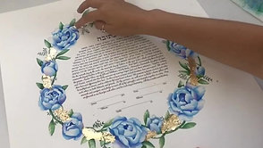 Applying gold leaf to a custom floral watercolour Ketubah