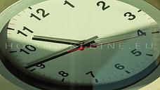 Close up to a wall clock, with running time pointer
