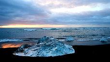 Jokulsarlon Bay Icebergs with waves crashing and Seal Swimming