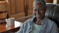 videoblocks-beautiful-happy-elderly-senior-black-woman-in-her-50s-or-60s-smiling-and-laughing-at-the-camera-while-sitting-on-her-living-room-sofa-during-the-day_sllk5fy7q_1080__D