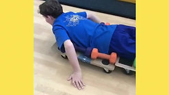 This client must maintain his posture on a scooter board to use his upper body strength to propel himself forward.