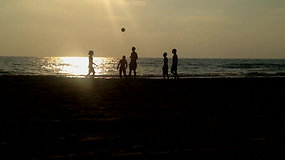 Playing Kickball At The Beach During Sunset