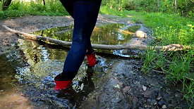 Girl in jeans and rubber boots in the mud