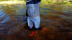 Girl in jeans and rubber boots in deep water