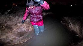 girl in waders and snobord pants in deep water