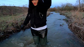 Girl in leather pants and waders in deep water