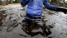 Girl in a snowboard suit and rubber boots in the water