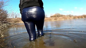 Girl in leather leggings and rubber boots in the water