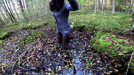 Girl in denim overalls and rubber boots in a swamp
