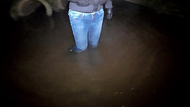 Girl in jeans and rubber boots in a swamp