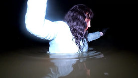 WetLook girl in white jeans and rubber boots in deep water