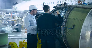 stock-footage-aircraft-maintenance-engineer-and-mechanic-inspecting-and-working-on-airplane-jet-engine-in-hangar
