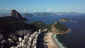 take from Leme beach shows Sugarloaf Mountain, tilt down to busy streets and beach