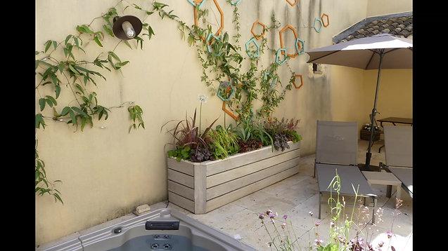 Treillage décoratif en bois et plantes grimpantes dans une petite cour de village provençal