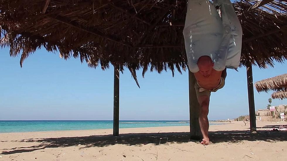 סרגיי מתרגל עם הערסל אנטיגראוויטי בחוף הים
