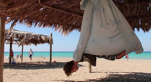 דוד מתרגל עם הערסל אנטיגראוויטי בחוף הים