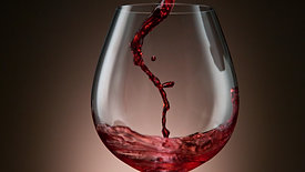 Camera follows red wine pouring into glass