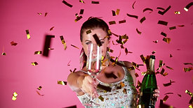 excited brunette woman with falling confetti dancing and jumping