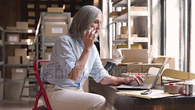stock-footage-older-female-dropshipping-business-owner-using-laptop-talking-on-phone-in-warehouse-mature-woman
