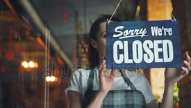 stock-footage-business-owner-attractive-woman-in-apron-hanging-we-re-open-sign-on-front-door-smiling-welcoming